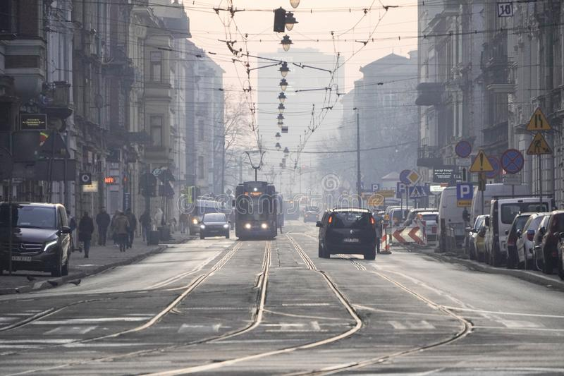 Krakow, Poland, 12.17.2019: the tram rides in a foggy European city, lights hanging over the roadway. city public transport royalty free stock images