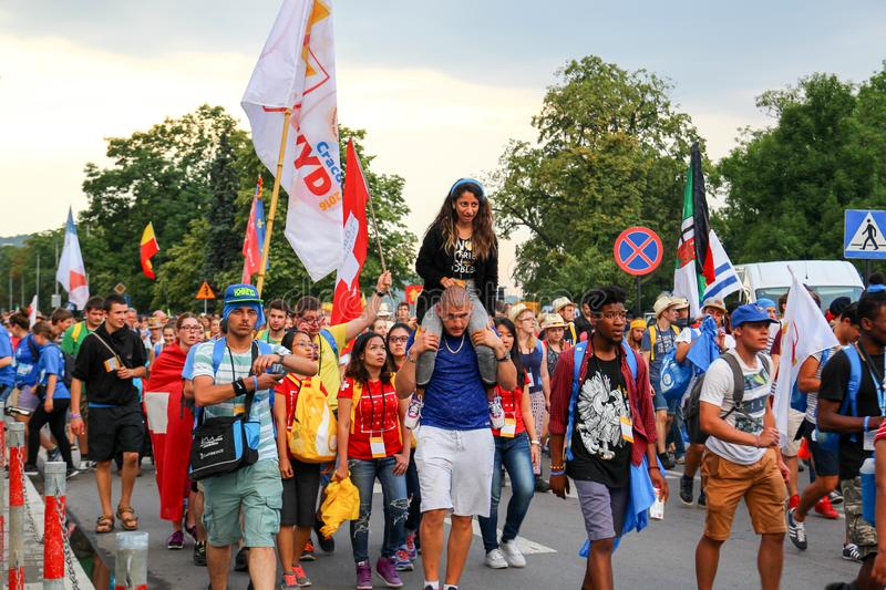 KRAKOW, POLAND - 2016 - World Youth Day 2016, A crowd of people. With flags, the guy carries on his shoulders a girl royalty free stock image
