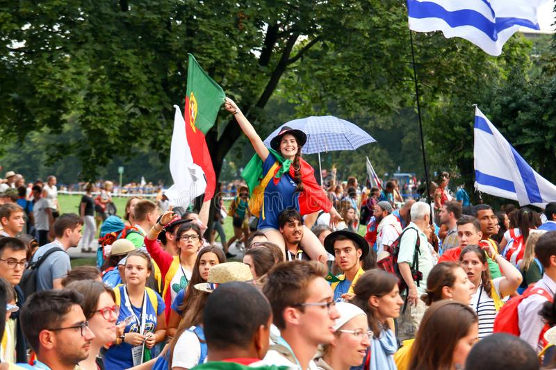 KRAKOW, POLAND - 2016 - World Youth Day 2016, A crowd of people. With flags, the guy carries on his shoulders a girl with the flag of Portugal stock photography