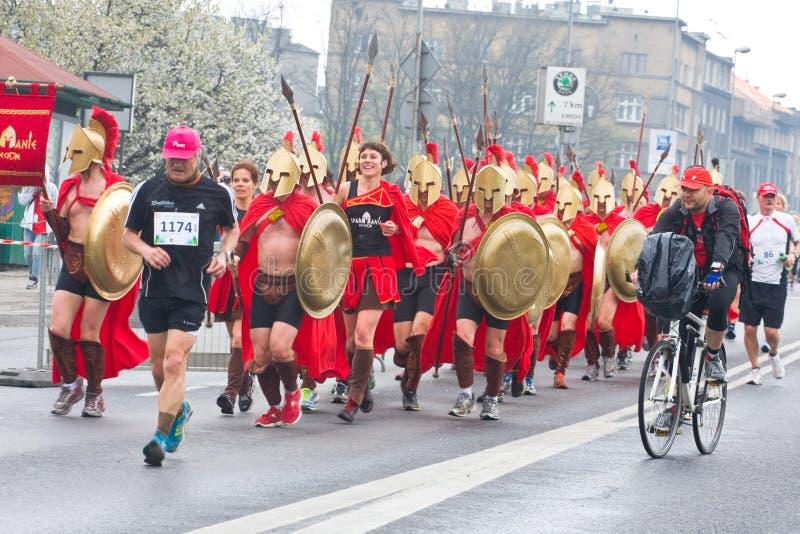 KRAKOW POLEN - APRIL 28: Cracovia maraton. Hastighet för grupp för Spartans barnvälgörenhet på stadsgatorna arkivbilder