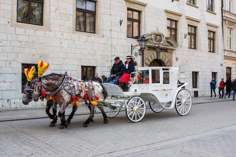 Krakow Polen - April 21, 2017: Hästar med hästdragna vagnar i gammal stad i Krakow Krakow är andra - störst och en av royaltyfri foto