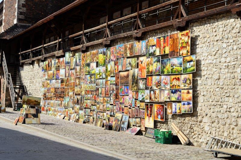 Krakow Polen - Augusti 7, 2013: På porten av St Florians säljer konstnärer deras målningar royaltyfri fotografi