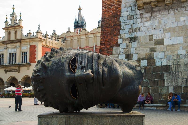 KRAKOW, POLEN: Eros Bendato, jättelik staty i Rynek Glowny, Krakow Brons noggin skulpterades av Igor Mitoraj 1999 och royaltyfria foton
