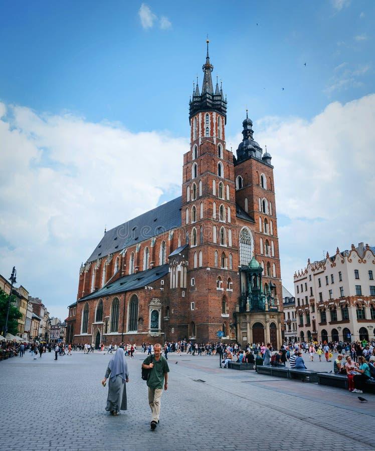 KRAKOW POLEN - JUNI 28, 2016: Folket går framme av St Mary Church (den Mariacki kyrkan) på huvudsaklig marknadsfyrkant på trevlig arkivbild