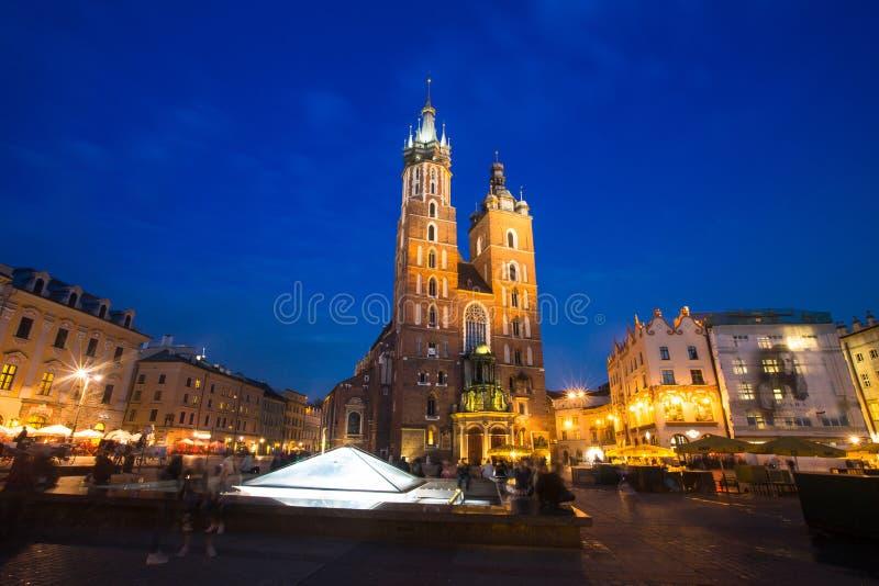 KRAKOW POLEN - Sts Mary kyrka på Rynek Glowny (marknadsfyrkant) i nattetid fotografering för bildbyråer