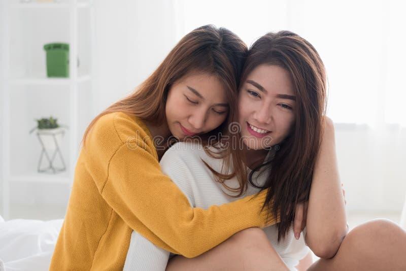Kram och sammanträde för Asien lesbisk lgbtpar på säng nära den vita windoen royaltyfria foton