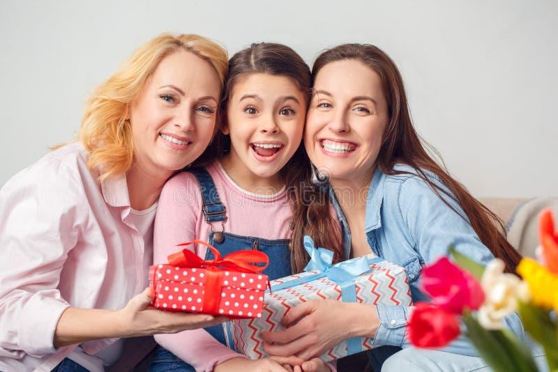 Krama för hemmastadd beröm för för farmormoder och dotter tillsammans sittande rymma gåvor royaltyfri fotografi