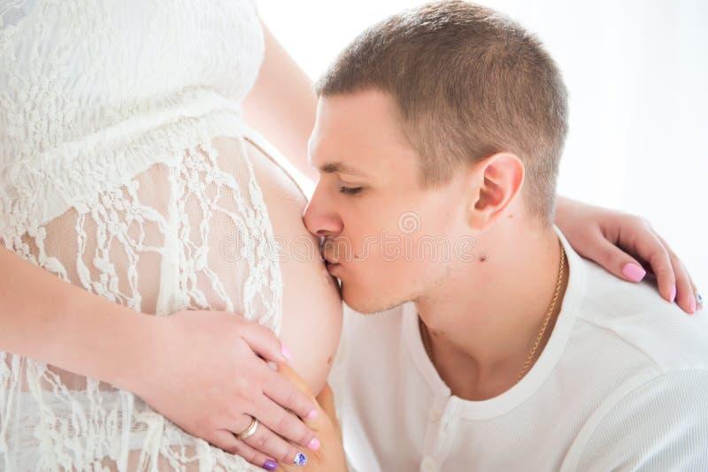 Krama för make och kyssande gravid buk av hans fru, närbildstående royaltyfri foto