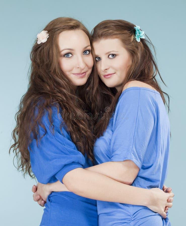 Krama för två ungt kvinnligt vänner som ser royaltyfri foto