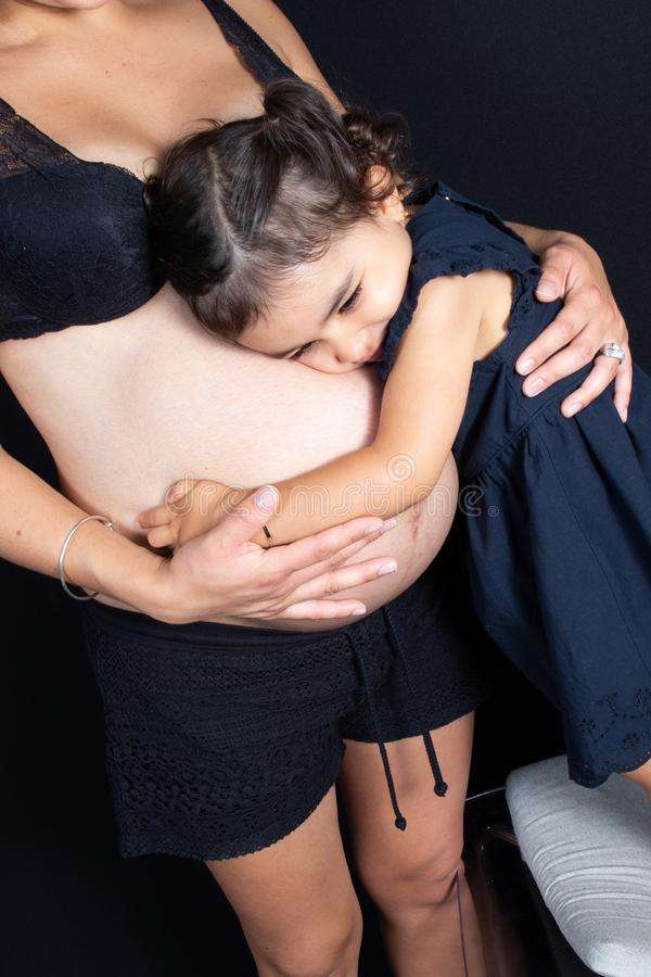 Kramdotterflicka som buktar modern som är gravid med förälskelse och mjukhet royaltyfri bild