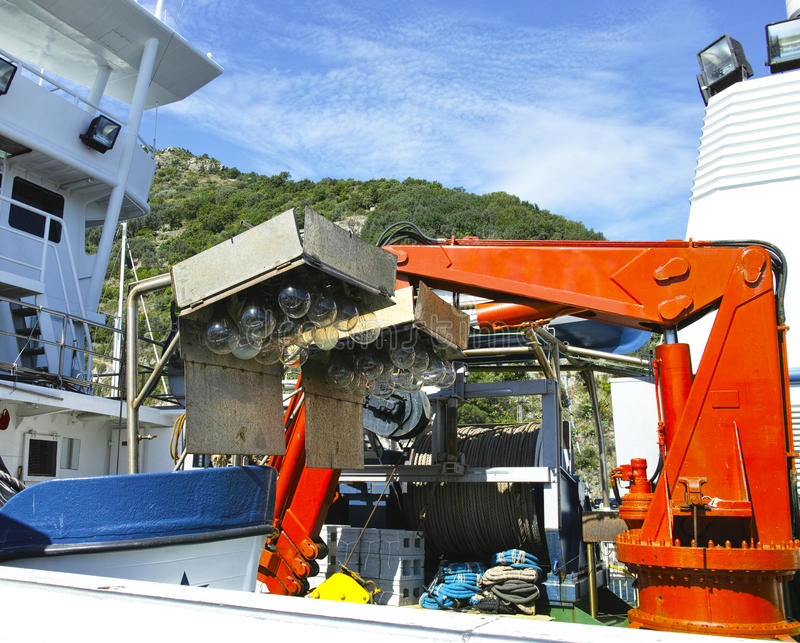 Kran överst en fiskebåt arkivbild