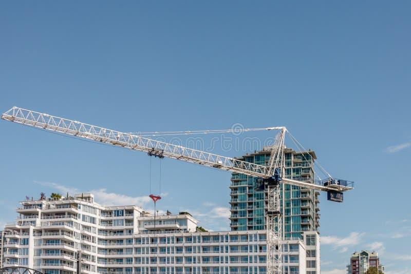 Kran errichtet moderne hohe Gebäude und Gebäude auf einem summe lizenzfreie stockfotografie