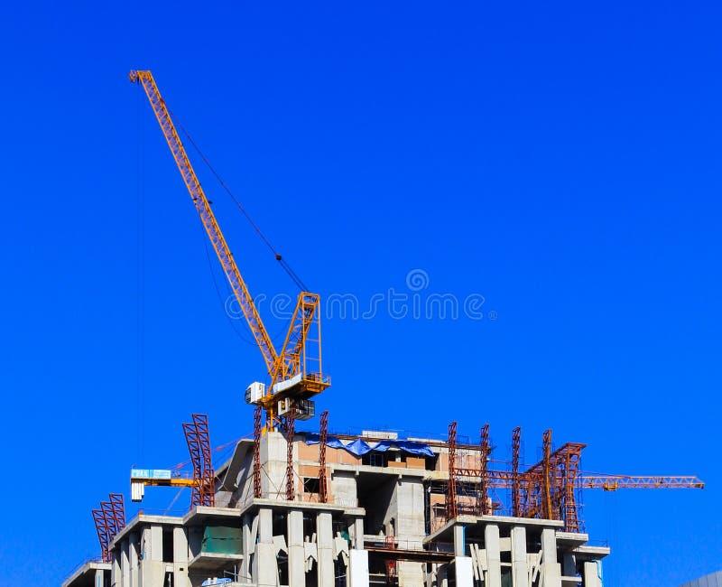 Kran och arbetare på konstruktionsplatsen mot blå himmel. arkivfoto