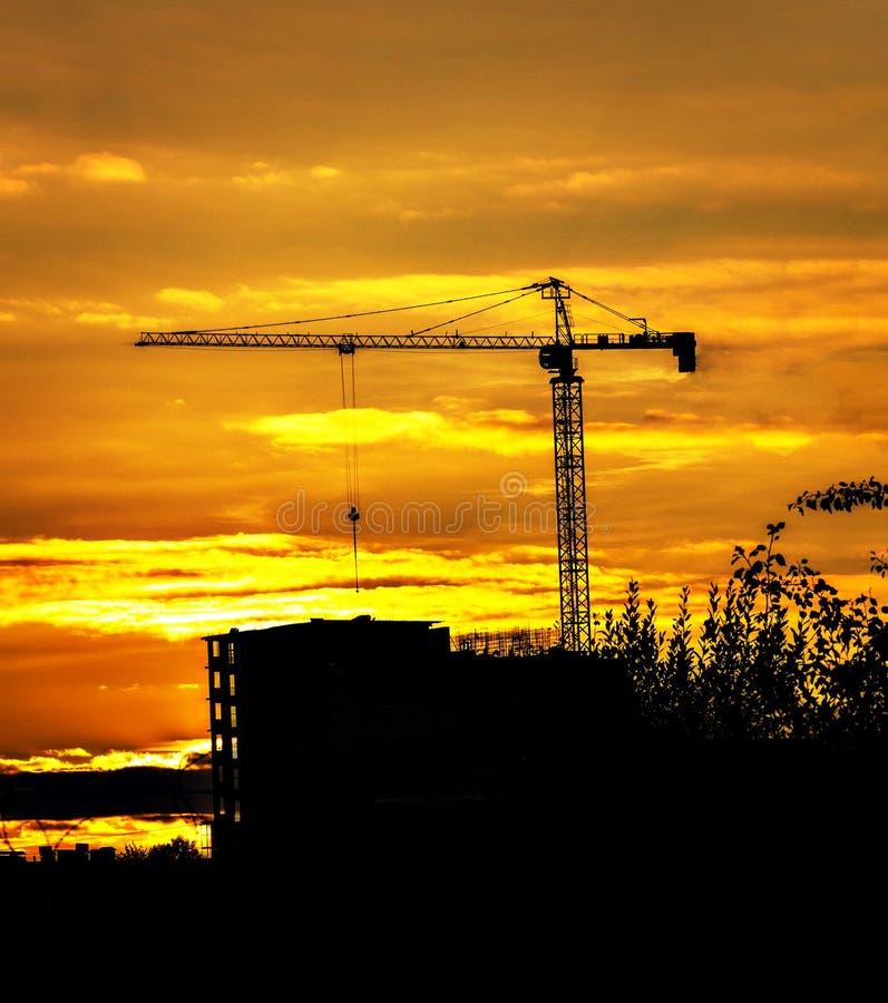 Kran- och byggnadskonturer över solen på solnedgången i sommar royaltyfri fotografi