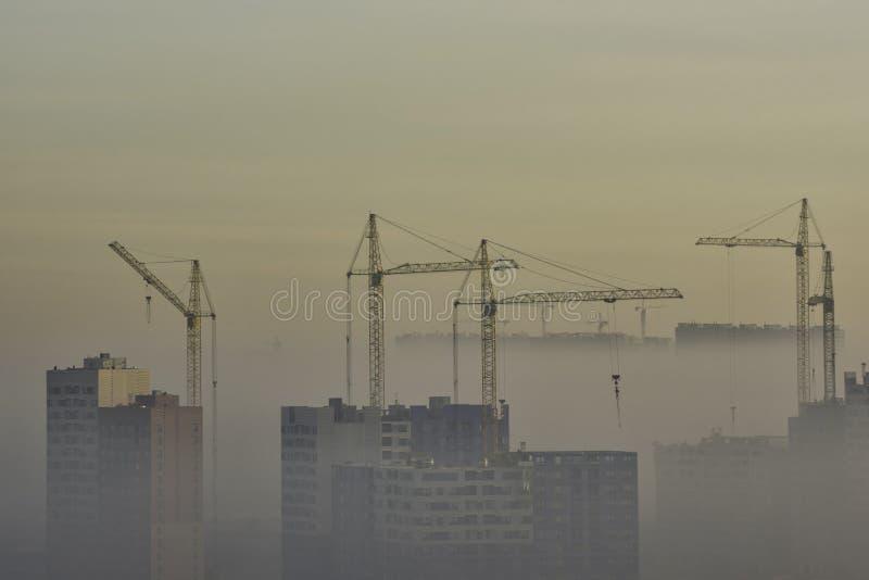 Kran- och konstruktionsplats i stads- smog arkivbild