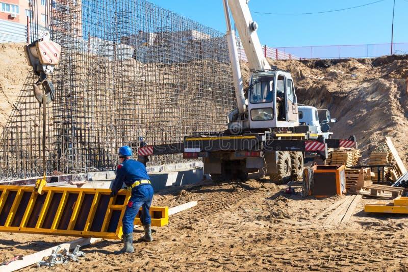 Kran und Arbeitskraft, die an einer Baustelle arbeiten stockbilder