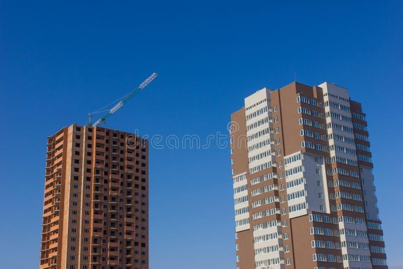 Kran und Hochbausite gegen blauen Himmel stockfotografie