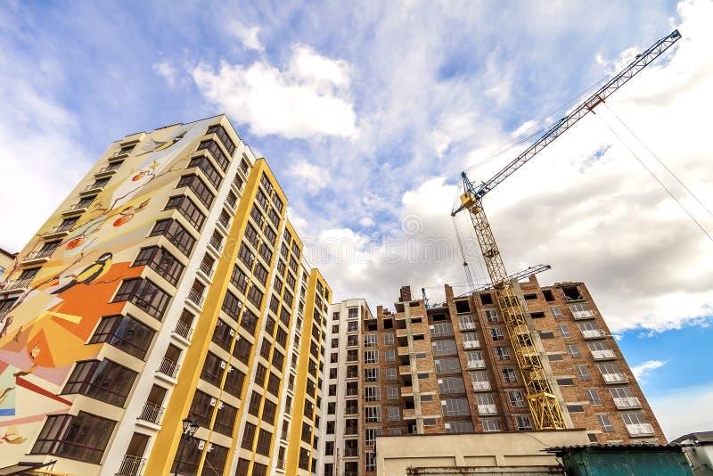 Kran und hoher Aufstieg, die im Bau gegen blauen Himmel errichten stockfotografie