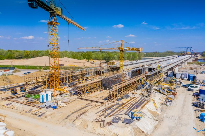 Kranar i konstruktionen av en bro för en huvudväg flyg- sikt arkivbild