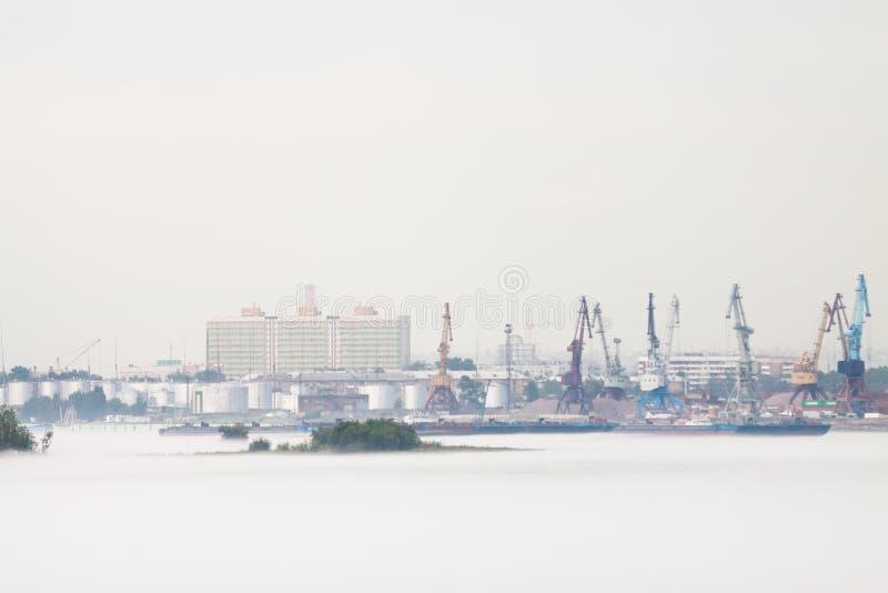 Kranar och industriellt rusar in porten, mot en bakgrund av molnigt v?der med dimma i sommaren Ryssland arkivfoto