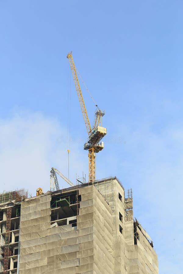 Kranen in bouwwerf met blauwe hemel stock fotografie