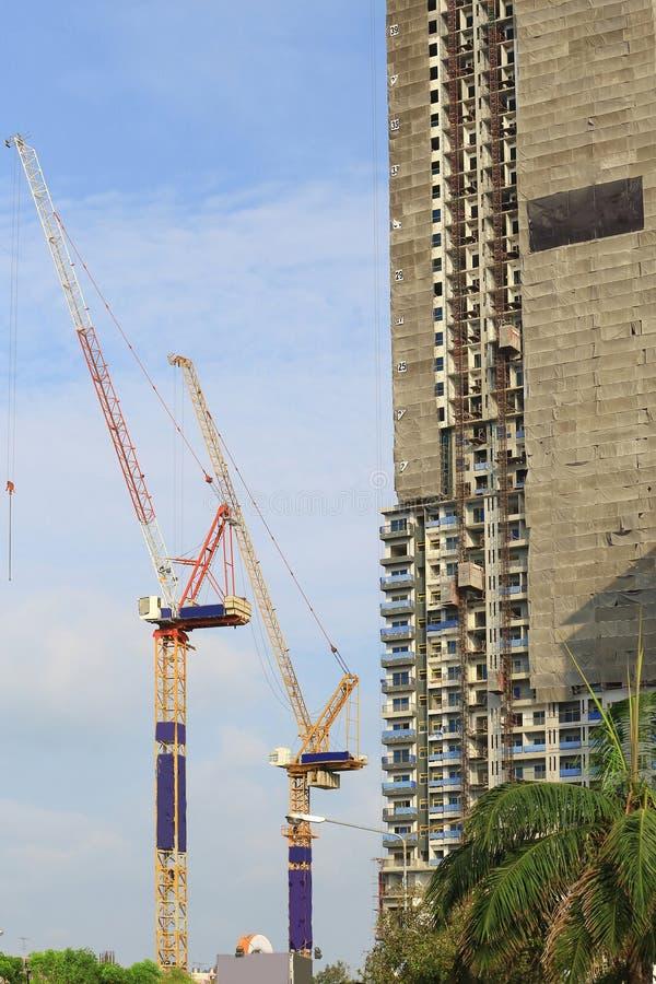Kranen in bouwwerf met blauwe hemel en wolk stock foto's