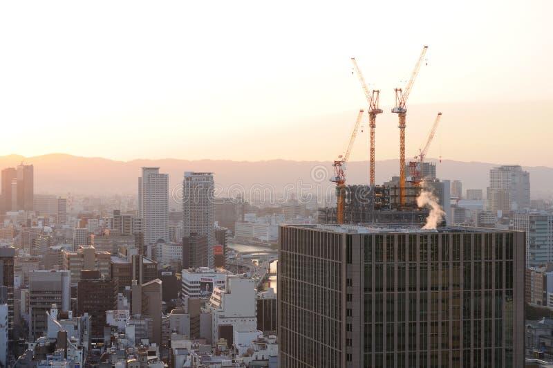 Kranen boven op een lang gebouw in Osaka stock afbeelding