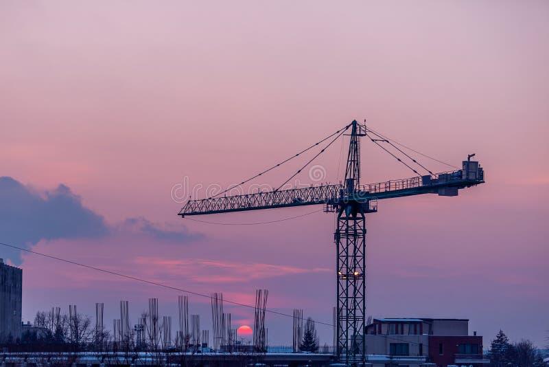 Kranen på solnedgången i idustrialized är av staden arkivbild