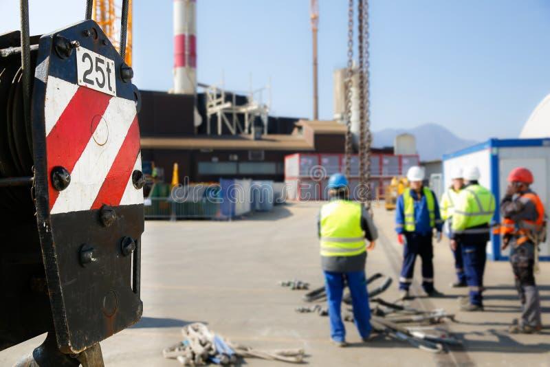 Kranflaschenzug mit Arbeitskräften im Hintergrund lizenzfreie stockfotografie