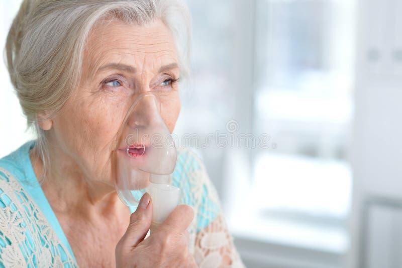 Kranke ältere Frau, die Einatmung macht lizenzfreie stockfotos
