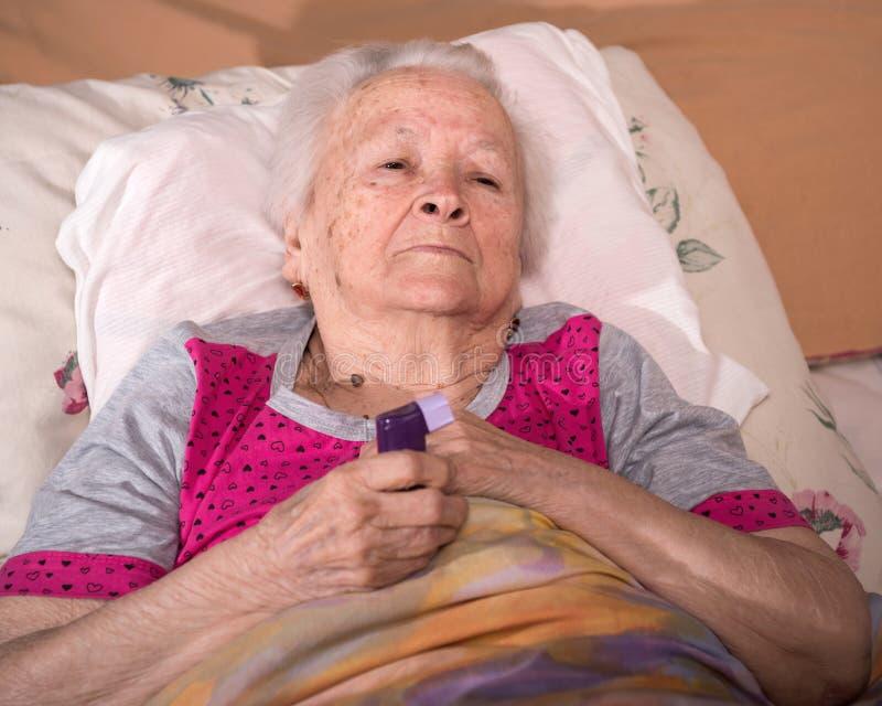 Kranke ältere Frau, die im Bett liegt und Asthmainhalator hält lizenzfreie stockbilder