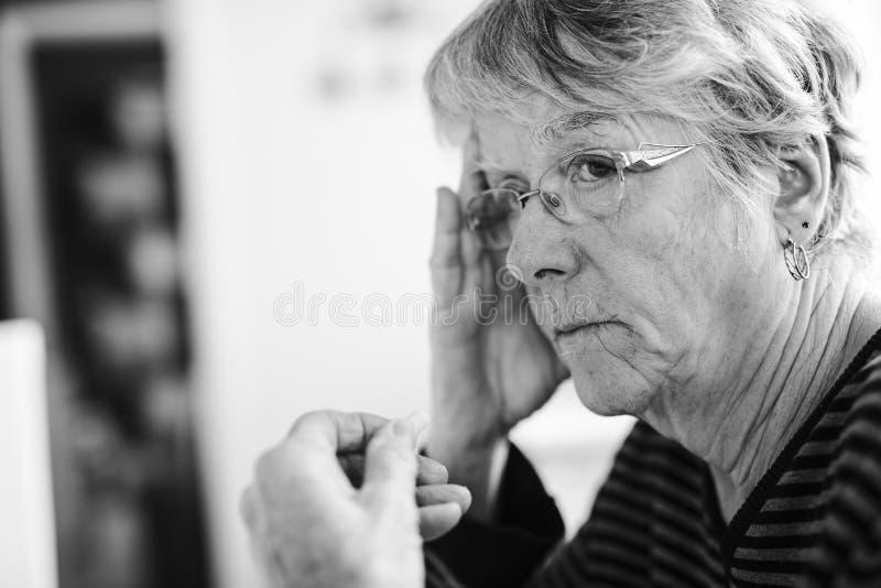 Kranke ältere Frau, die zu Hause ihre Pillen einnimmt lizenzfreie stockbilder