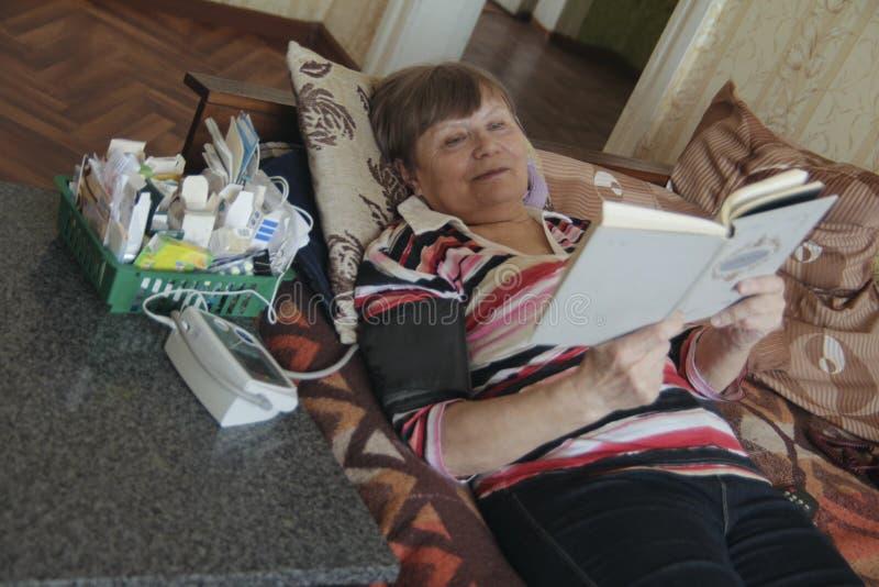 Kranke ältere Frauenlesung am Bett mit Tabletten und Gerät für das Messen des Drucks lizenzfreie stockfotografie
