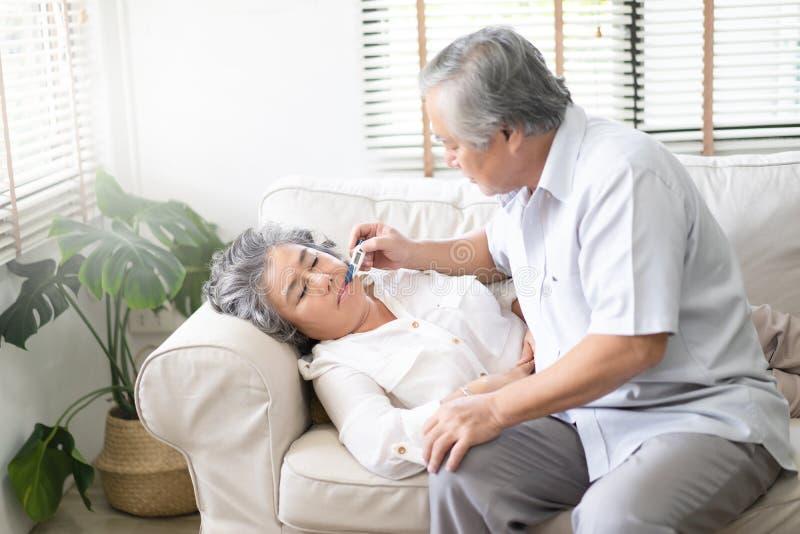 Kranke alte Frau mit dem Thermometer, der in Sofa- und Ehemannhand legt stockfoto