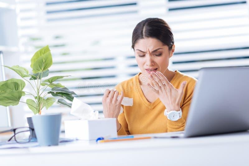 Kranke Arbeitskraft, die beim Sitzen vor einem Laptop und Fühlen unwohl niest lizenzfreie stockbilder