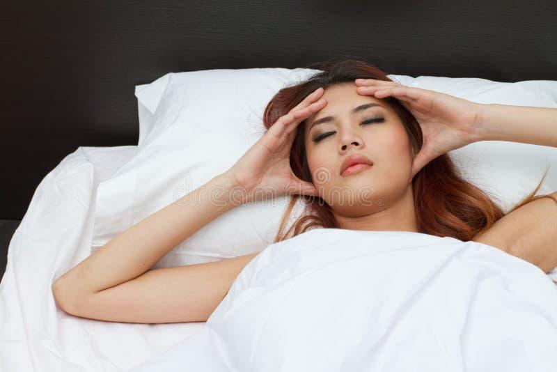 Kranke Frau auf dem Bett, ihren Kopf massierend lizenzfreies stockfoto