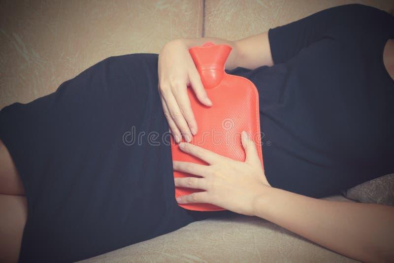 Kranke Frau, die auf Sofa mit Heißwassertasche liegt stockfotografie