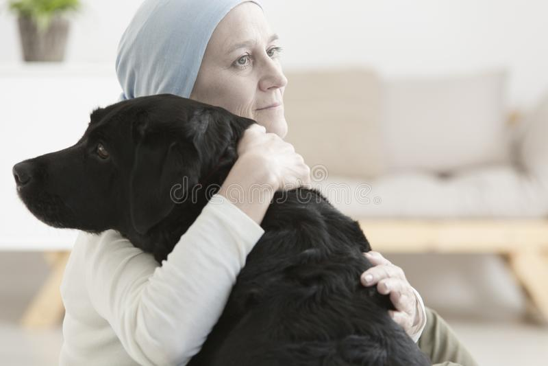 Kranke Frau, die Hund umarmt stockbilder