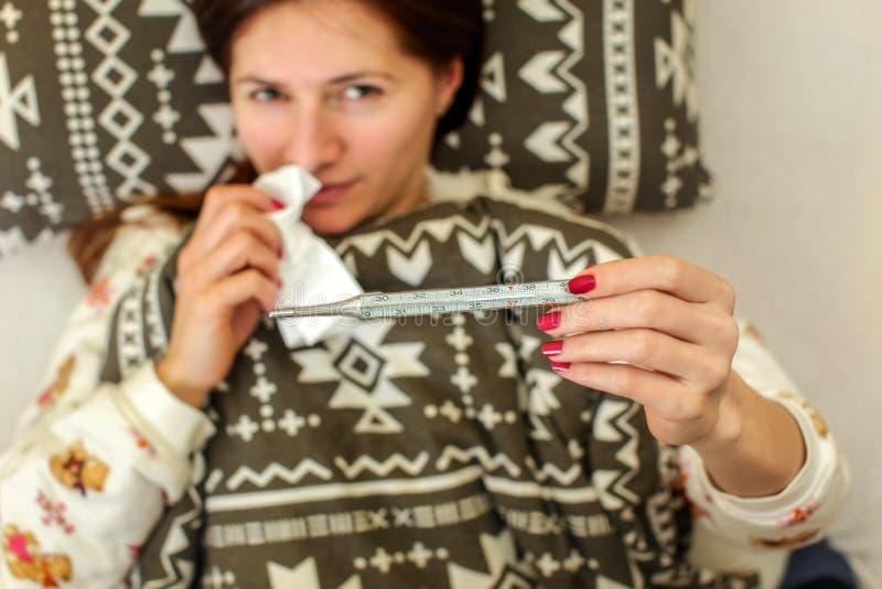 Kranke Frau, die im Bett, bedeckt mit Daunendecke liegt lizenzfreie stockfotos