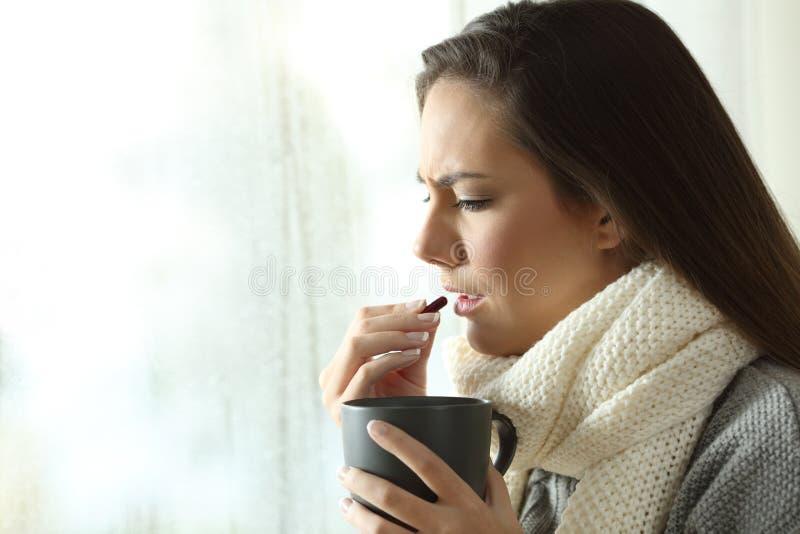 Kranke Frau, die zu Hause eine Pille im Winter einnimmt stockfoto