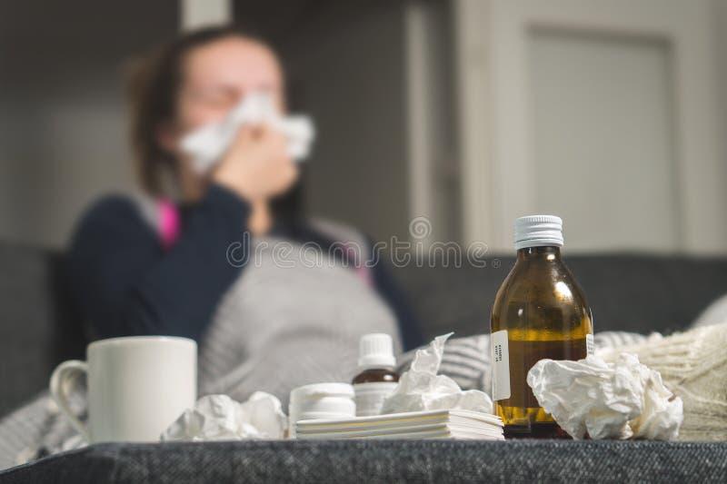 Kranke Frau, die zum Gewebe niest Medizin, Heißgetränk und schmutziges lizenzfreies stockfoto