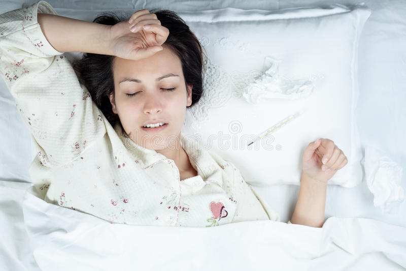 Kranke Frau im Bett lizenzfreies stockbild