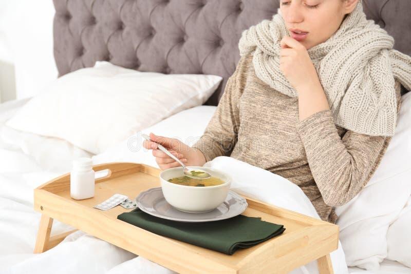 Kranke junge Frau, die Suppe isst, um Kälte im Bett zu kurieren stockbild