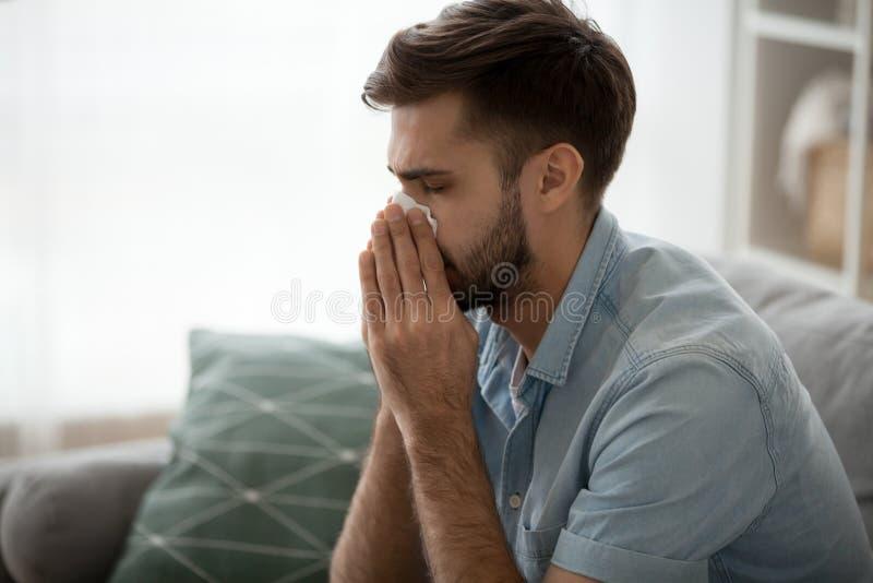 Kranke Mannschlagnase, die unter Fieber oder Grippe leidet stockfoto