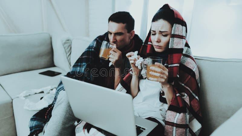 Kranke Paare, die auf Sofa in den karierten Decken sitzen Trinkende Medizin Kranke Frau Weißes Sofa im Raum Unglücklicher Kerl kr stockfoto