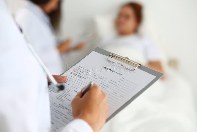 Krankengeschichteliste stationären Patienten weiblichen Medizindoktors füllende stockfoto