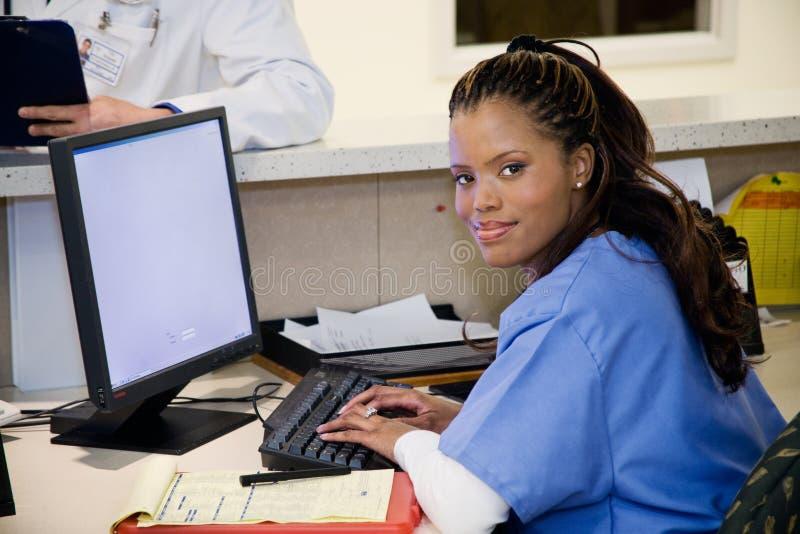 Krankenhaus: Lächelnde Krankenschwester am Klinik-Arbeitsplatz lizenzfreie stockbilder
