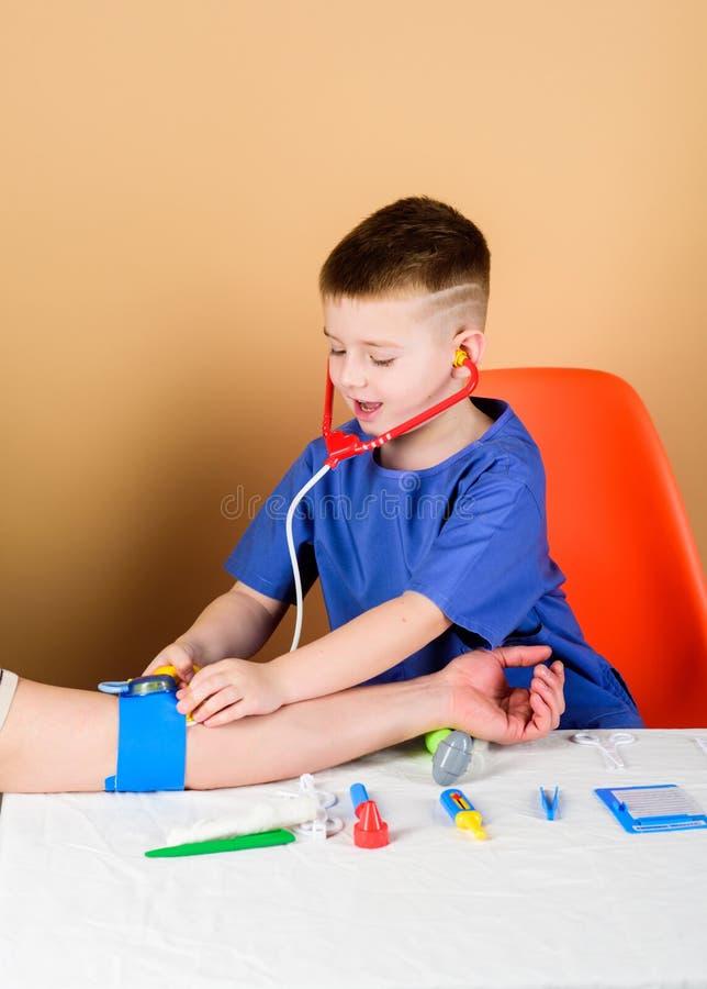 Krankenhaus Medizin und Gesundheit Kinderarztinternierter wenig Junge in der medizinischen Uniform Krankenschwesterlaborassistent stockfotos