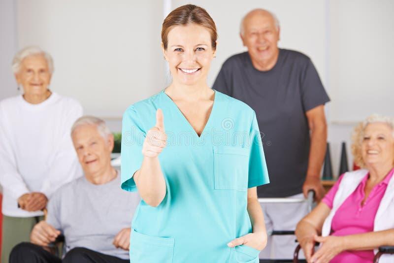 Krankenpflegeassistent, der Daumen oben vor älteren Leuten hält lizenzfreie stockfotografie