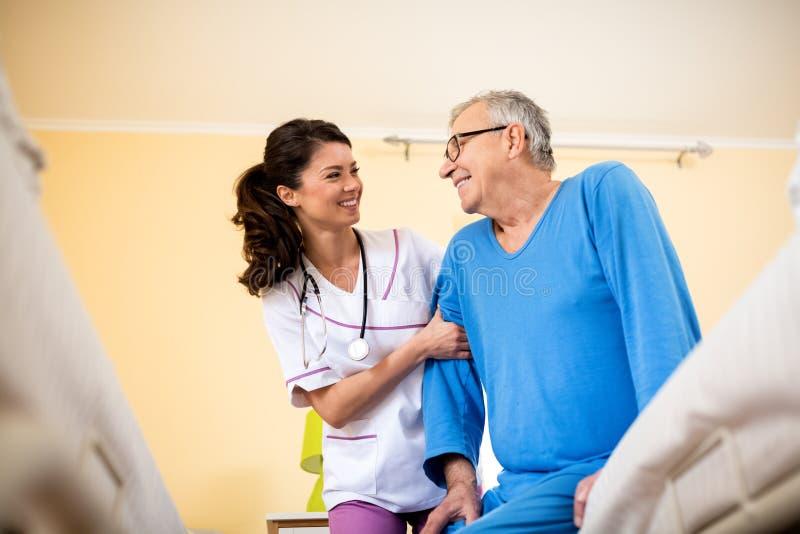 Krankenschwester am älteren Mann der Krankenpflegehaushaltshilfen stockbild